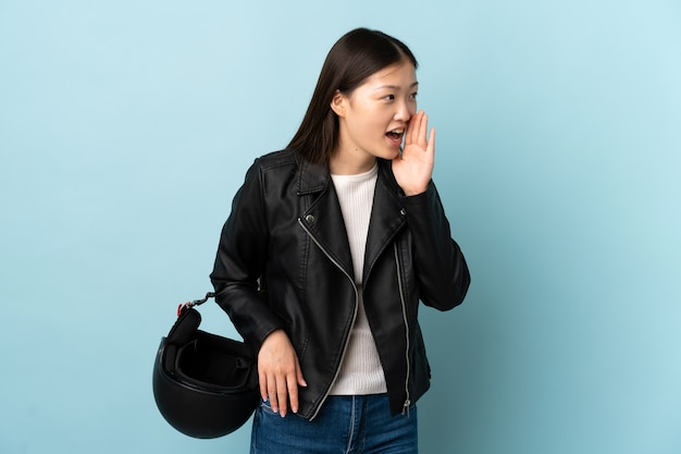 Chinese woman holding a motorcycle helmet over blue shouting with mouth wide open