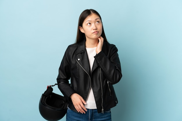 Chinese woman holding a motorcycle helmet over blue thinking an idea