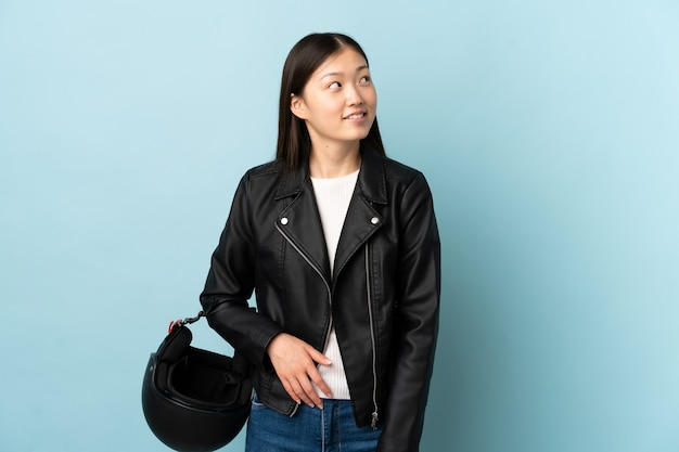 Chinese woman holding a motorcycle helmet over isolated blue background laughing and looking up