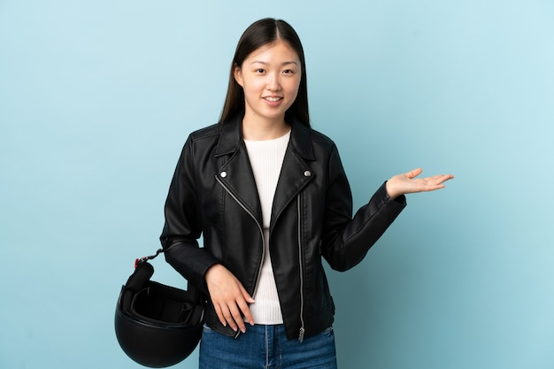 Chinese woman holding a motorcycle helmet over isolated blue holding copyspace imaginary on the palm