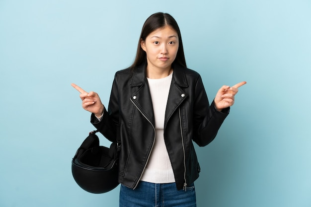 Chinese woman holding a motorcycle helmet on isolated blue pointing to the laterals having doubts