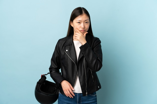 Chinese woman holding a motorcycle helmet over isolated blue wall thinking an idea