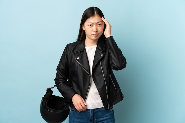 Chinese woman holding a motorcycle helmet over isolated blue wall unhappy and frustrated with something. negative facial expression