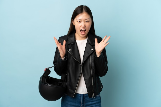 Chinese woman holding a motorcycle helmet over isolated blue wall unhappy and frustrated with something