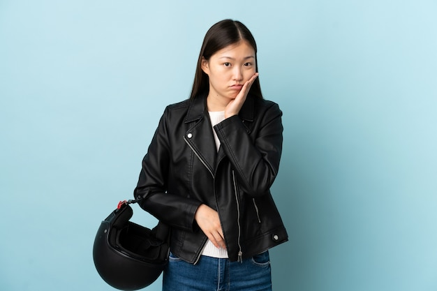 Chinese woman holding a motorcycle helmet over isolated blue wall unhappy and frustrated