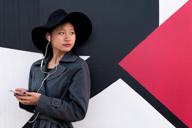 Китайская женщина слушает музыку в наушниках