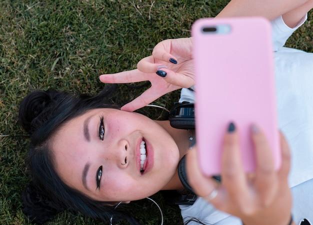 Китайская женщина фотографирует на траве
