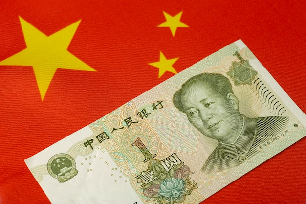 Chinese yuan against the backdrop of the chinese flag. one yuan. chinese currency and economy concept