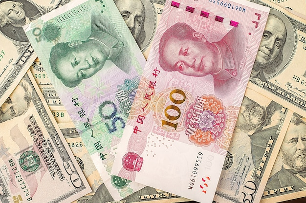 Chinese yuan bank note on usa dollars background