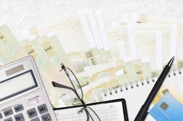 Купюры китайского юаня и калькулятор с очками и ручкой