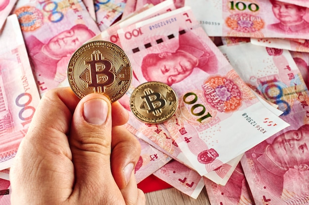 Chinese yuan money and cryptocurrency bitcoin close-up. digital virtual internet currency investment concept
