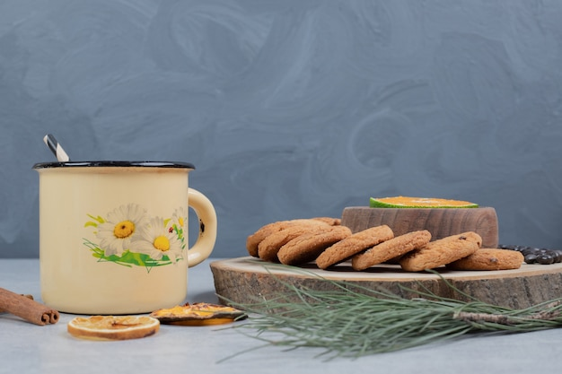 Chip cookies, tazza di tè e fetta di mandarino su sfondo grigio. foto di alta qualità