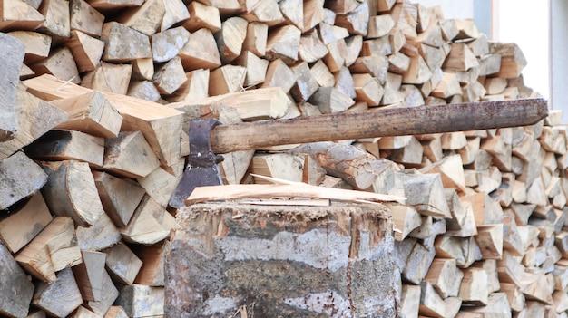 Колотые дрова на зиму для отопления. топор вонзается лезвием в пень. тесак с деревянной ручкой. сбор урожая в колхозе. уложенные штабелями сухие дрова для отопления дома.