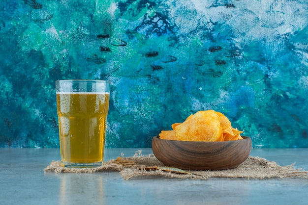 大理石の背景に、テクスチャのチップスとビール。
