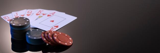 反射のある黒い背景のカジノで遊ぶためのチップとカード
