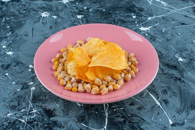 青いテーブルの上の皿の上のチップスとひよこ豆。