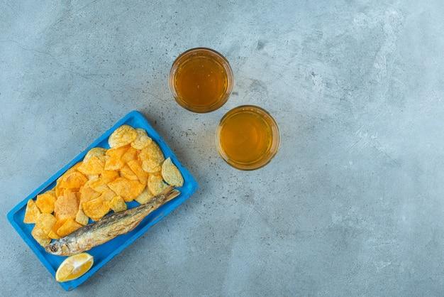 大理石のテーブルの上で、ビール2杯の横にある木の板にチップと魚。