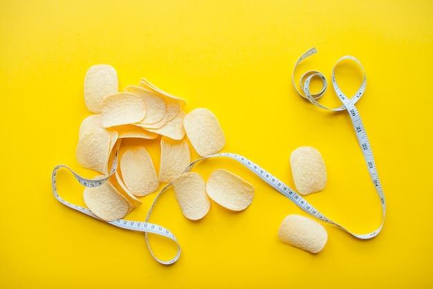 밝은 노란색 배경 체중 감량 및 다이어트 개념에 칩과 측정 테이프