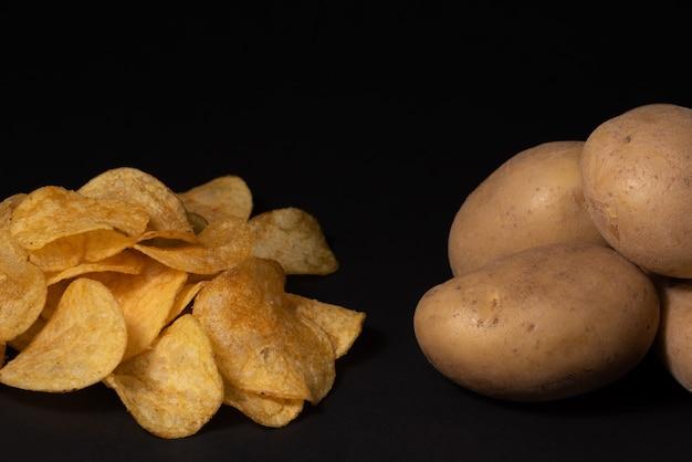 Чипсы и клубни картофеля на черном фоне