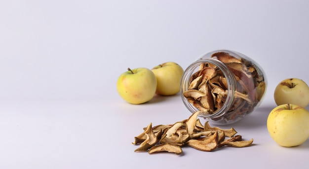 Chips apples in a glass jar and pieces of this fruits on a white space, horizontal format, space for text