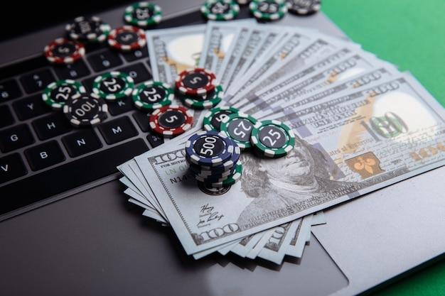 ポーカーオンラインまたはカジノギャンブルのクローズアップ用のチップ、紙幣、ラップトップ。オンラインポーカーのコンセプト。
