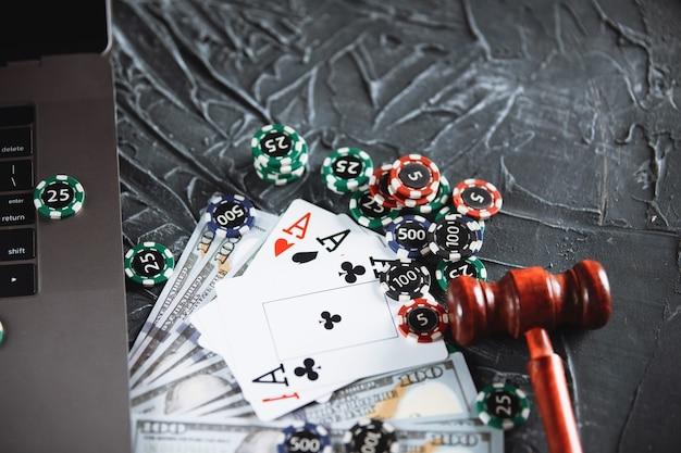オンラインポーカーやカジノギャンブル用のチップ、紙幣、ラップトップ。オンラインポーカーのコンセプト。