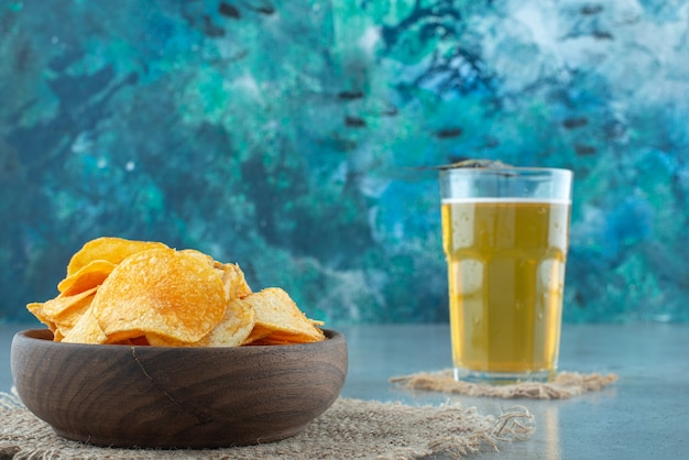 Chips in a bowl next to glass of beer , on the marble table.