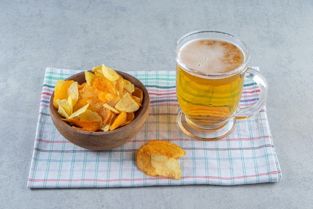 Chips in a bowl next to glass of beer on a tea towel , on the marble surface..