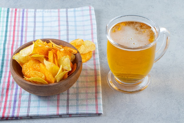 Chips in a bowl next to glass of beer on a tea towel , on the marble surface.