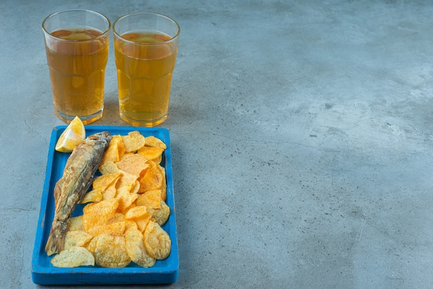 Chips and fish on a wooden plate next to two glasses of beers , on the marble table.
