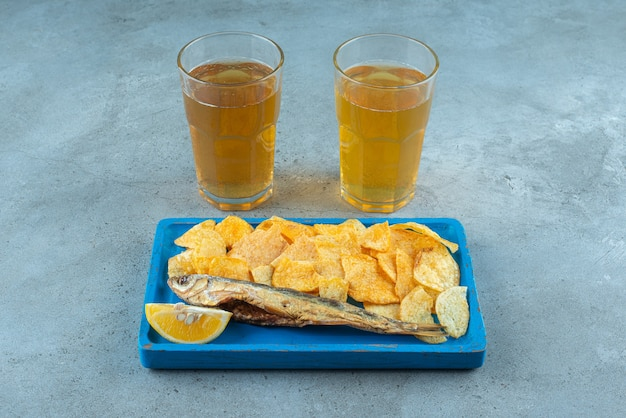 Chips and fish on wooden plate next to two glasses of beers on marble. Free Photo