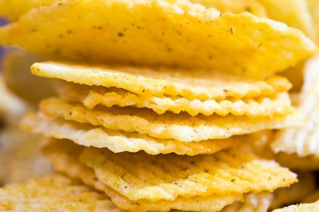 Чипсы из настоящего картофеля в специях и ароматизаторах для улучшения вкуса, чипсы обычные с гофрированной поверхностью