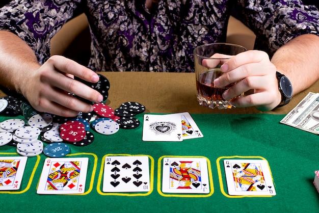 Фишки в руках человека на покерном столе