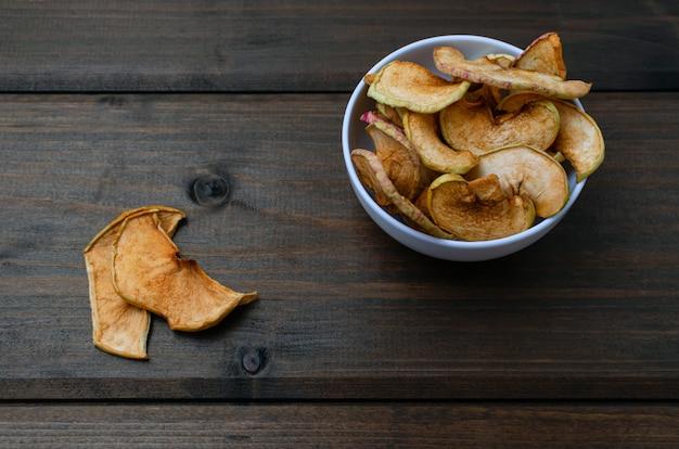 Чипсы яблок с корицей лежат на белой тарелке на столе из черных деревянных досок. органические яблочные чипсы. сухофрукты. здоровая сладкая закуска.