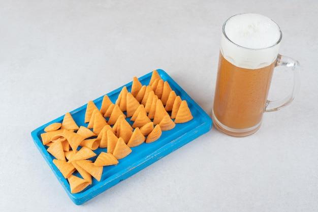 Piatto di patatine fritte e bicchiere di birra sulla superficie della pietra.