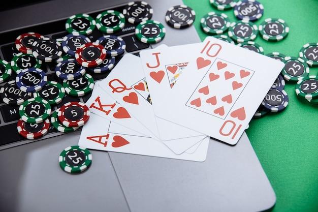 オンラインポーカーやカジノギャンブル用のチップ、トランプ、ラップトップ。オンラインポーカーのコンセプト。