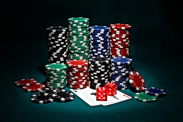 Chips for poker with pair of aces and dice