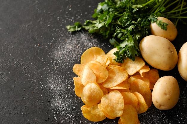 칩 준비. 바삭 바삭한 음식 칩 요리. 녹색 허브를 곁들인 짠 능선 튀김 조각과 신선한 유기농 감자