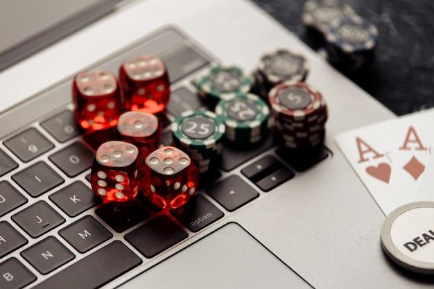 ポーカーオンラインまたはカジノギャンブルのクローズアップ用のエース付きの赤いサイコロとトランプをチップします