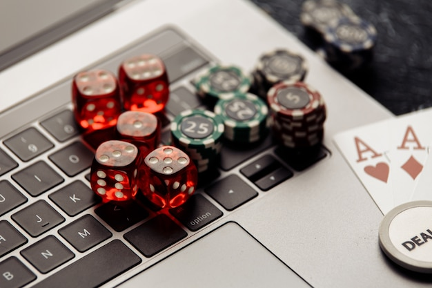 Chips red dices and playing cards with aces for poker online or casino gambling closeup
