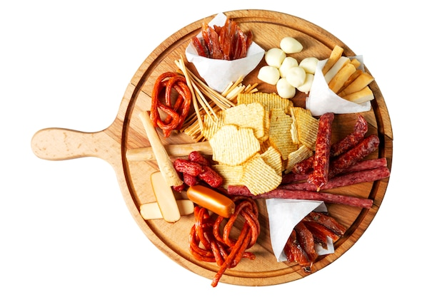 Chips, sausages and cheeses on a wooden board