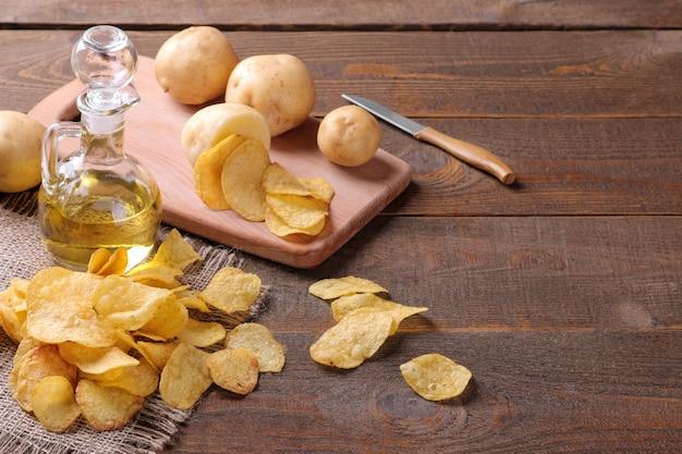 Чипсы с маслом и свежим картофелем на коричневом деревянном столе