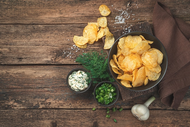 Chips with dill, sour cream and garlic on a wooden background. appetizer for beer. top view, copy space.