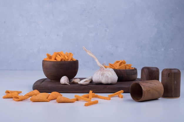 Чипсы со вкусом чеснока на деревянной доске
