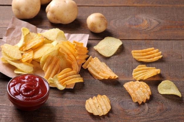 Чипсы с красным соусом и свежим картофелем на коричневом деревянном столе