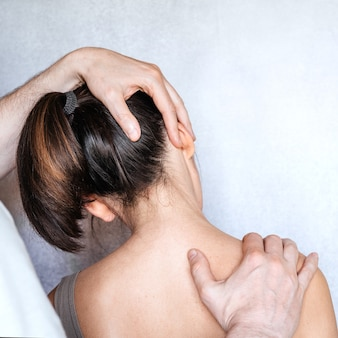 A chiropractor performing a manipulation on woman's neck and administering of spinal adjustments to relive neck pain