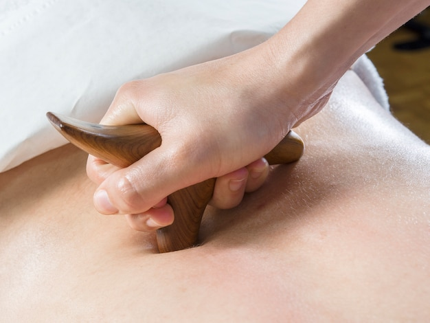 Chiropractor, physiotherapist is giving a back massage with a wood tool. alternative medicine.