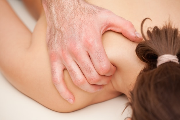 Chiropractor squeezing the shoulder of woman while massaging