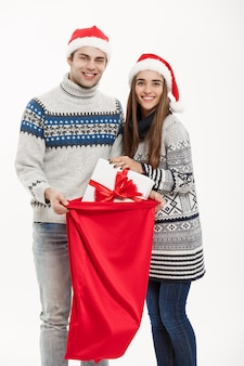 Chirstmas concept - young attractive couple with santa red bag celebrating chirstmas day. isolated on white background.