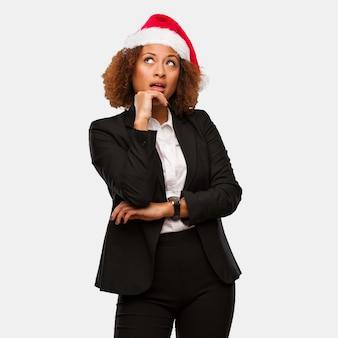 アイデアを考えてchirstmasサンタの帽子を着て若いビジネス黒人の女性